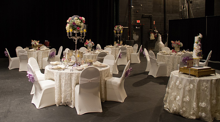 White wedding tables with purple flowers on chairs