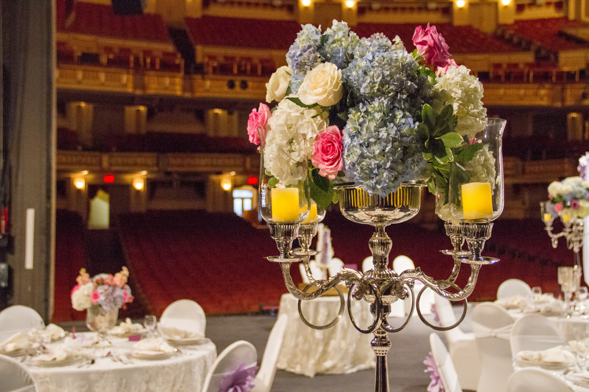 White tables on stage with flower centerpieces