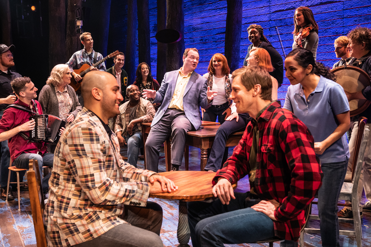Come From Away gathered around tables