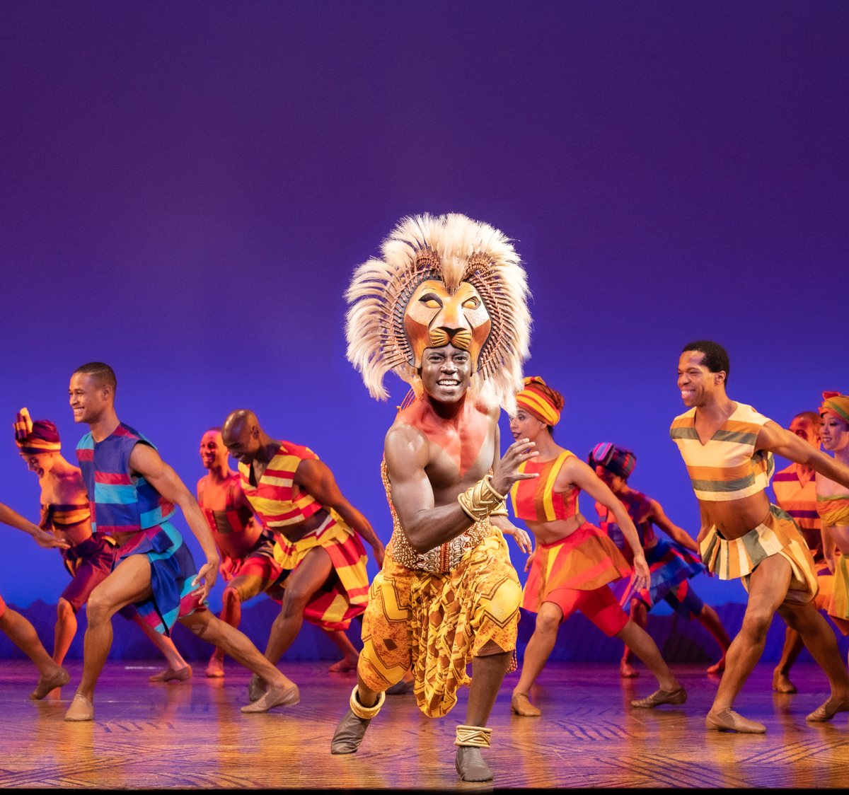 The Lion King, lion and background dancers performing.