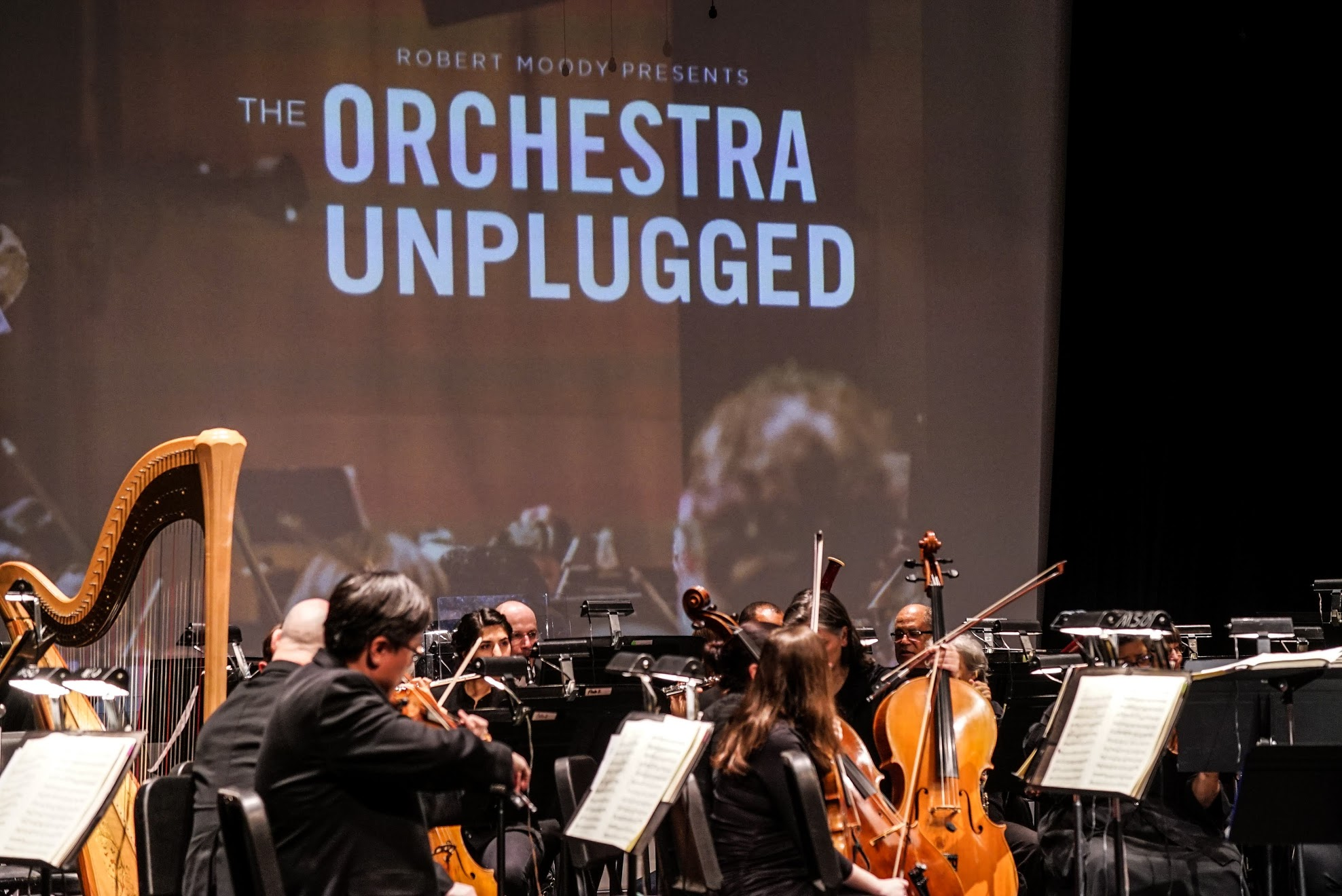 Orchestra playing with Orchestra Unplugged Logo projected onto screen.